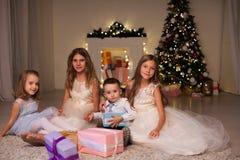 Der kleine Junge und drei Mädchenkinderoffene Weihnachtsgeschenk Weihnachtsbaum Winter des neuen Jahres stockfotos