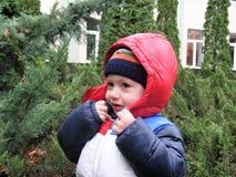 Der kleine Junge versucht, die Haube zu umklammern Lizenzfreies Stockbild