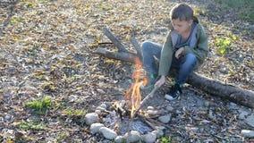Der kleine Junge wirft Holz in das Feuer zur Tageszeit stock video footage