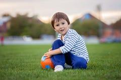 Der kleine Kleinkindjunge, der Fußball und Fußball, Spaß habend spielt, übertreffen Stockfoto
