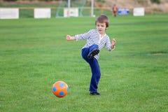 Der kleine Kleinkindjunge, der Fußball und Fußball, Spaß habend spielt, übertreffen Stockbild
