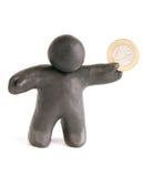 Der kleine Mann mit der einer Euromünze gemacht vom Plasticine Stockfotografie