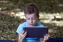 Der kleine nette Junge, der im Park sitzt und spielen sein Lieblingsspiel O Lizenzfreies Stockfoto