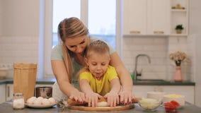 Der kleine schöne blonde Junge hilft Mutter zu kochen Mutter und Sohn in den bunten Hemden sind bereitstellen den Teig Mutter ist stock footage