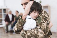 Der kleine Sohn nimmt von seinem Vater Abschied, der zum Militärdienst geht Lizenzfreie Stockfotografie