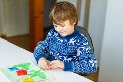 Der Kleinkindjunge, der Papierorigamitulpe macht, blüht für eine Postkarte für Mutter ` s Tag oder Geburtstag Nettes Kind von gru Stockfoto