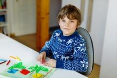 Der Kleinkindjunge, der Papierorigamitulpe macht, blüht für eine Postkarte für Mutter ` s Tag oder Geburtstag Nettes Kind von gru Lizenzfreies Stockbild