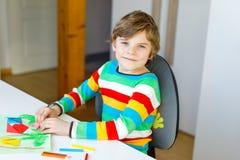 Der Kleinkindjunge, der Papierorigamitulpe macht, blüht für eine Postkarte für Mutter ` s Tag oder Geburtstag Nettes Kind von gru Stockfotos