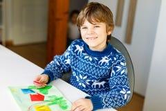 Der Kleinkindjunge, der Papierorigamitulpe macht, blüht für eine Postkarte für Mutter ` s Tag oder Geburtstag Nettes Kind von gru Lizenzfreie Stockbilder