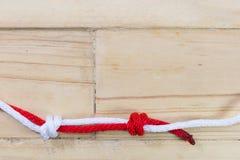 Der Knoten des Fischers gemacht mit rotem Seil auf hölzernem Hintergrund Stockfotografie