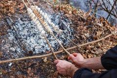 Der Koch bereitet den Teig auf Aufsteckspindeln auf dem Wald des Feuers im Frühjahr zu stockfoto