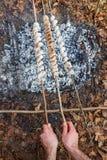 Der Koch bereitet den Teig auf Aufsteckspindeln auf dem Wald des Feuers im Frühjahr zu lizenzfreies stockbild