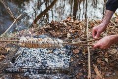 Der Koch bereitet den Teig auf Aufsteckspindeln auf dem Wald des Feuers im Frühjahr zu stockbilder
