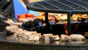 Der Koch dreht Stücke Fleisch auf Feuer stock video footage