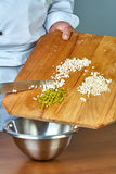 Der Koch gießt die Schnittbestandteile in eine Schüssel voll Rezepte für Lebensmittelrezepte Stockfotos