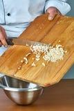 Der Koch gießt die Schnittbestandteile in eine Schüssel voll Rezepte für Lebensmittelrezepte Stockfotografie