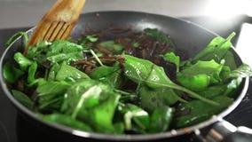 Der Koch macht Gemüseteller mit der Zwiebel, die im Balsamico-Essig gebraten wird und addiert Spinat stock video