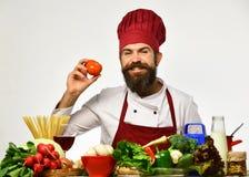 Der Koch, der rote Tomate hält Mann in der roten Kappe Lizenzfreie Stockfotografie