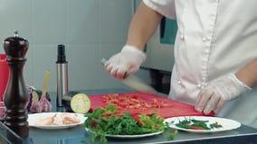 Der Koch schneidet eine Tomate für einen Salat stock video