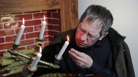 Der Kollektor betrachtet seinen Reichtum mit brennenden Kerzen stock footage