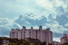 Der Komplex von hohen Gebäuden gegen den Himmel mit volumetrischen Wolken Lizenzfreies Stockfoto