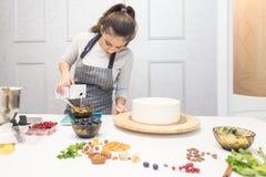 Der Konditor bereitet einen Schokoladenkekskuchen Creme verzierend vor Das Konzept des selbst gemachten Geb?cks, Kuchen kochend lizenzfreie stockfotos