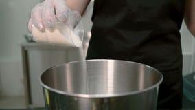 Der Konditor streut den Zucker vom Plastikglas in den Stahltopf stock footage
