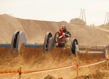 Der Konkurrent überwindt das Hindernis entlang dem Weg motorrad lizenzfreies stockbild
