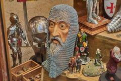 Der Kopf des alten Mannes abgedeckt durch die Masche schellt für Schutz umgeben durch andere Zahlen und Rüstungen der Zeit im Spe Lizenzfreie Stockfotos