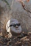 Der Kopf einer defekten Statue mit dunklen Gläsern lizenzfreie stockfotos