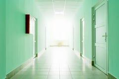 Der Korridor mit hellem Licht vom Fenster, eine Halle mit grünen Wänden und weiße Türen Lizenzfreies Stockfoto