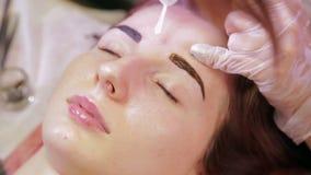 Der Kosmetiker malt den Kunden mit einer Augenbraue mit einer speziellen Bürste stock footage