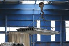 Der Kran bewegt ein Stahlbetonprodukt Lizenzfreies Stockfoto