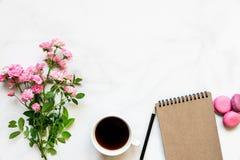 Der kreative Plan, der von der Rosarose gemacht wird, blüht Blumenstrauß, Kaffeetasse, leeres Notizbuch und Makronen Lizenzfreies Stockfoto