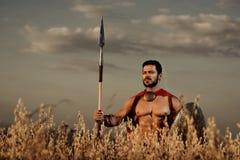 Der Krieger, der im roten Mantel tragen und die Rüstung mögen spartanisch stockfotografie