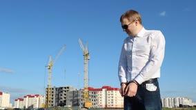 Der Kriminalkommissar in den schwarzen Gläsern steht in den Handschellen mit Gelddollar vor dem hintergrund des Baus stock video footage