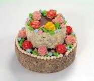 Der Kuchen wird mit purpurroten Rosen. verziert Stockfotografie