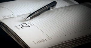 Der Kugelschreiber liegt auf der offenen Seite des täglichen Klotzes Lizenzfreie Stockbilder