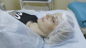 Der Kunde der Cosmetologyklinik liegt auf der Couch das Schalenverfahren erwartend stock footage