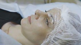 Der Kunde der Cosmetologyklinik liegt auf der Couch das Schalenverfahren erwartend stock video