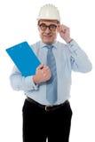 Der lächelnde gereifte Architekt anhalten sein Auge-tragen stockbilder