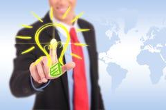 Der lächelnde Geschäftsmann, der eine Glühlampe drückt, knöpfen Stockbilder