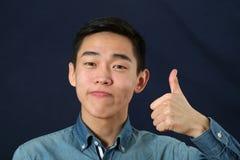 Der lächelnde junge asiatische Mann, der die Daumen gibt, up Zeichen Lizenzfreies Stockbild
