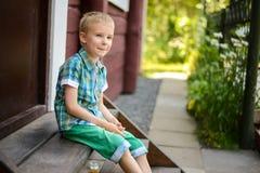 Der lächelnde junge blonde Junge, der auf Portal sitzt, tritt zu Hause Lizenzfreie Stockfotografie