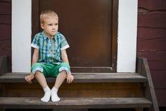 Der lächelnde junge blonde Junge, der auf Portal sitzt, tritt zu Hause Lizenzfreie Stockfotos