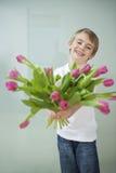 Der lächelnde Junge, der heraus Tulpe hält, blüht gegen grauen Hintergrund lizenzfreie stockfotos