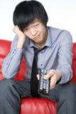 Der lächelnde junge Mann in einem grauen Hemd sieht Fern Stockbild