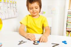 Der lächelnde Junge setzte Münzen auf Zahlen Zählung lernend Lizenzfreies Stockbild