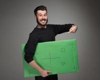 Der lächelnde Mann als Geschäftsmann mit grüner Platte Stockfoto