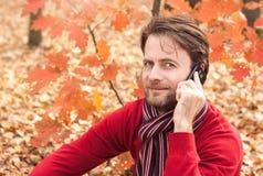 Der lächelnde Mann, der an einem Handy in einem Herbst spricht, parken Stockfotografie